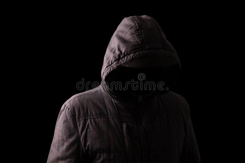 Hombre asustadizo y espeluznante que oculta en las sombras, con la cara y la identidad ocultadas imágenes de archivo libres de regalías