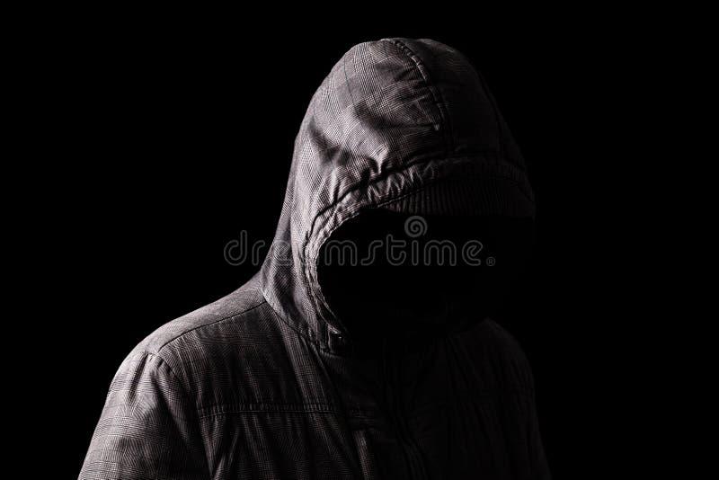 Hombre asustadizo y espeluznante que oculta en las sombras, con la cara y la identidad ocultadas con la capilla imagenes de archivo