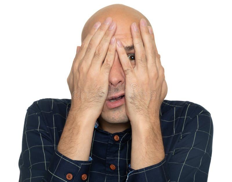 Hombre asustado que cubre su cara con las manos foto de archivo libre de regalías