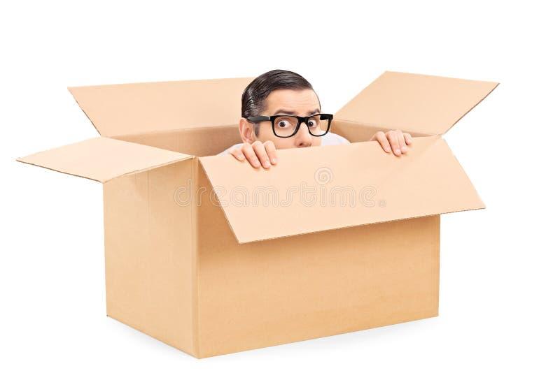 Hombre asustado que oculta en una caja del cartón fotografía de archivo