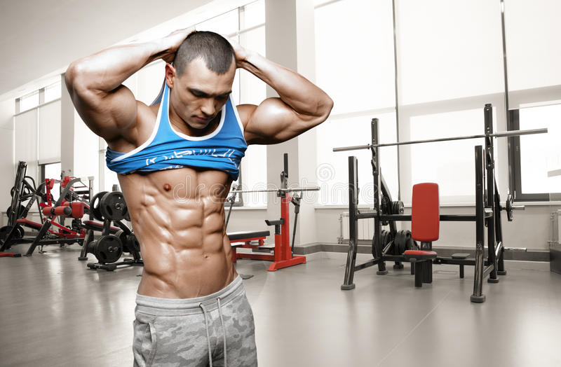 Hombre atlético brutal que toma la camisa apagado en el gimnasio imágenes de archivo libres de regalías