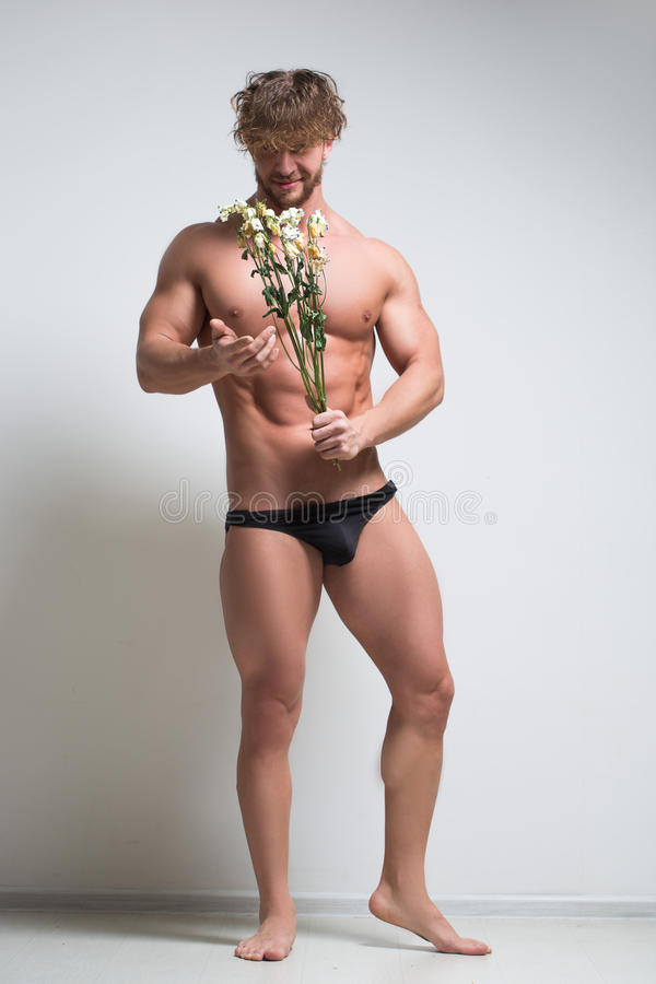 Hombre atlético con flores marchitadas imagen de archivo