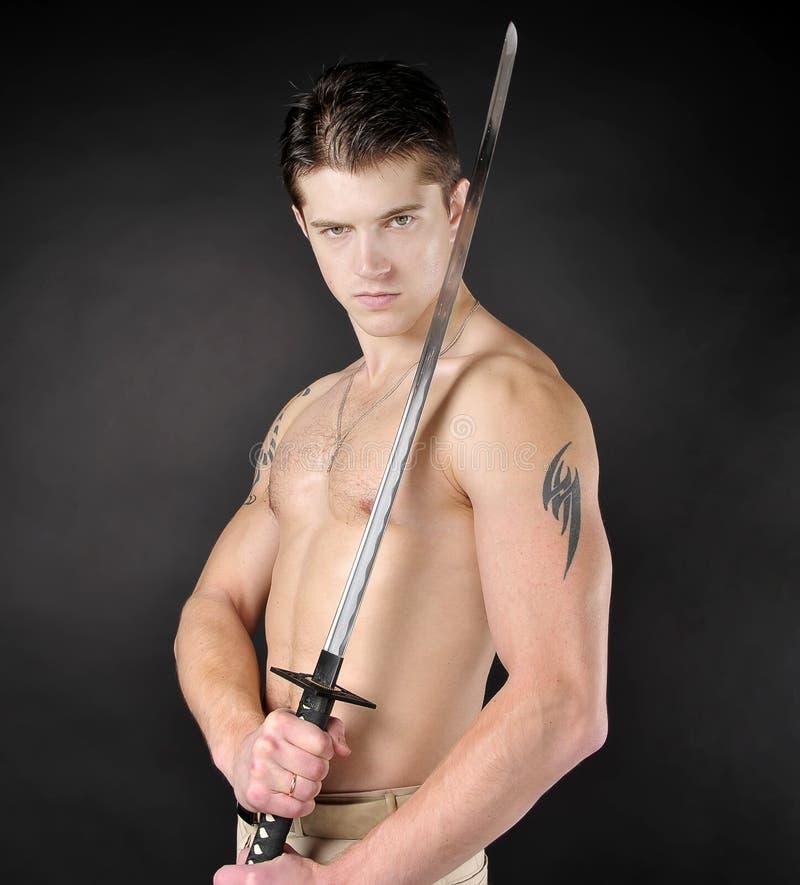 Hombre atlético con la espada. fotos de archivo