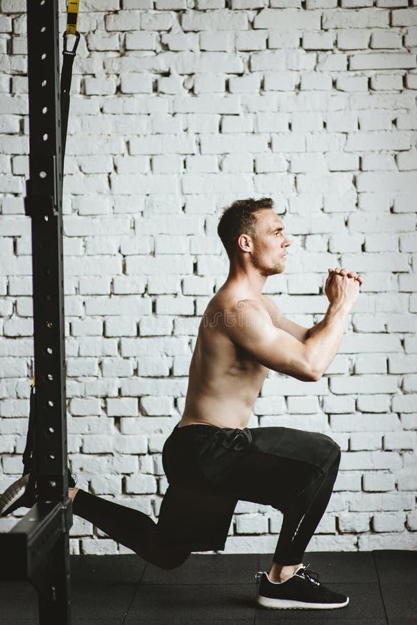 Hombre atlético con posiciones en cuclillas practicantes aptas del cuerpo muscular en gimnasio fotos de archivo