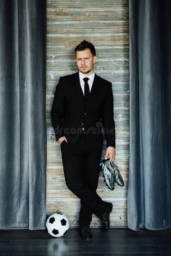 Hombre atlético elegante en un traje de negocios y un balón de fútbol Contra la perspectiva de una pared del desván imagen de archivo libre de regalías