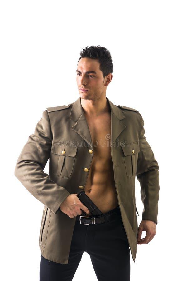 Hombre atlético en la chaqueta militar abierta que sostiene el arma fotografía de archivo