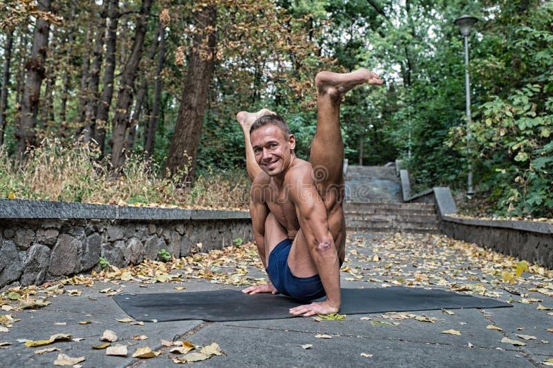 Hombre atlético flexible sonriente hermoso que hace asanas de la yoga en foto de archivo libre de regalías