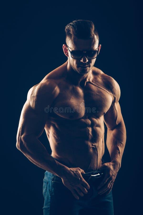 Hombre atlético fuerte en gafas de sol en negro fotografía de archivo