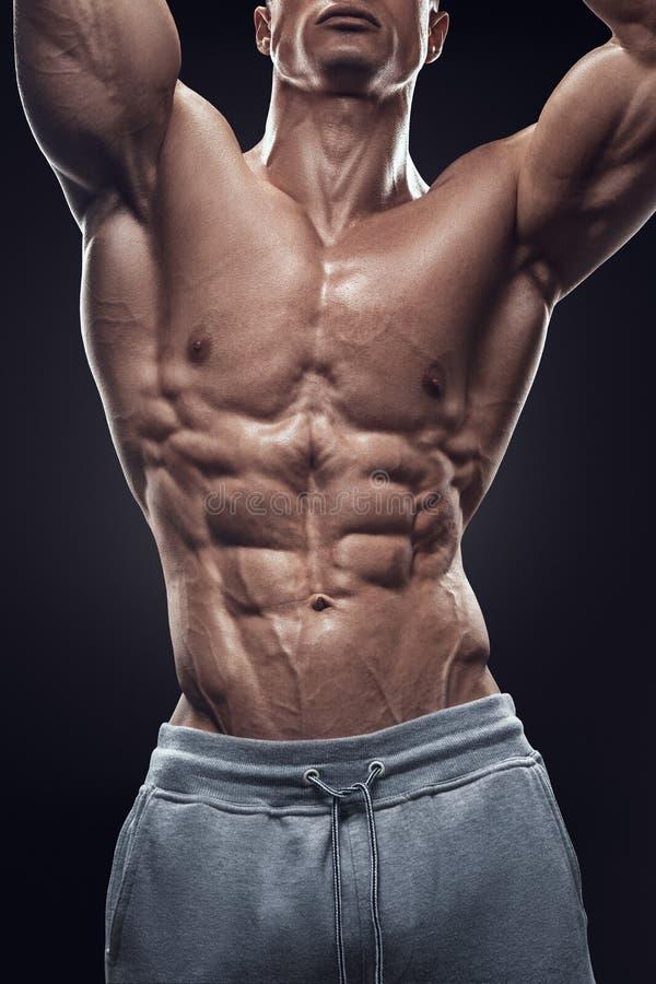 Hombre atlético hermoso que se resuelve con pesas de gimnasia fotografía de archivo