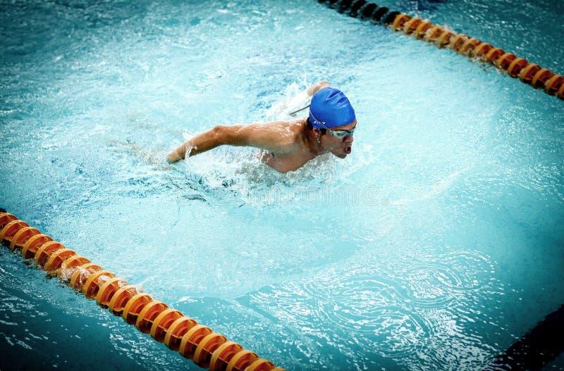 Hombre atlético joven con la natación de la mariposa fotos de archivo libres de regalías