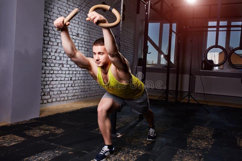 Hombre atlético joven en el entrenamiento del sportwear en el gimnasio apto de la cruz con los anillos contra la pared de ladrill imagen de archivo libre de regalías