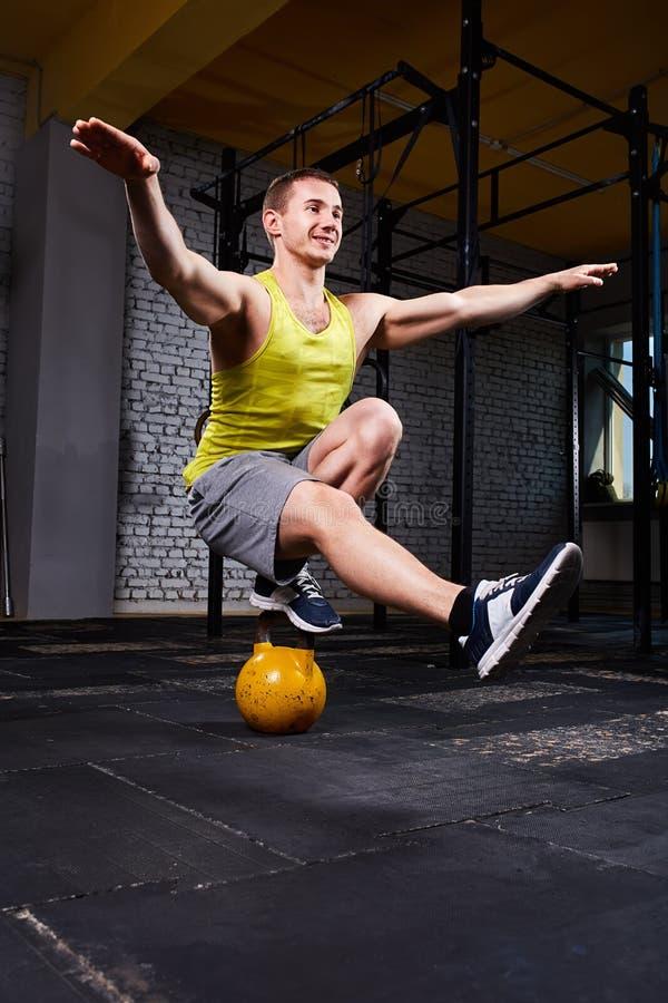 Hombre atlético joven que hace ejercicios en gimnasio apto de la cruz mientras que se agacha en una pierna en el kettlebell fotos de archivo