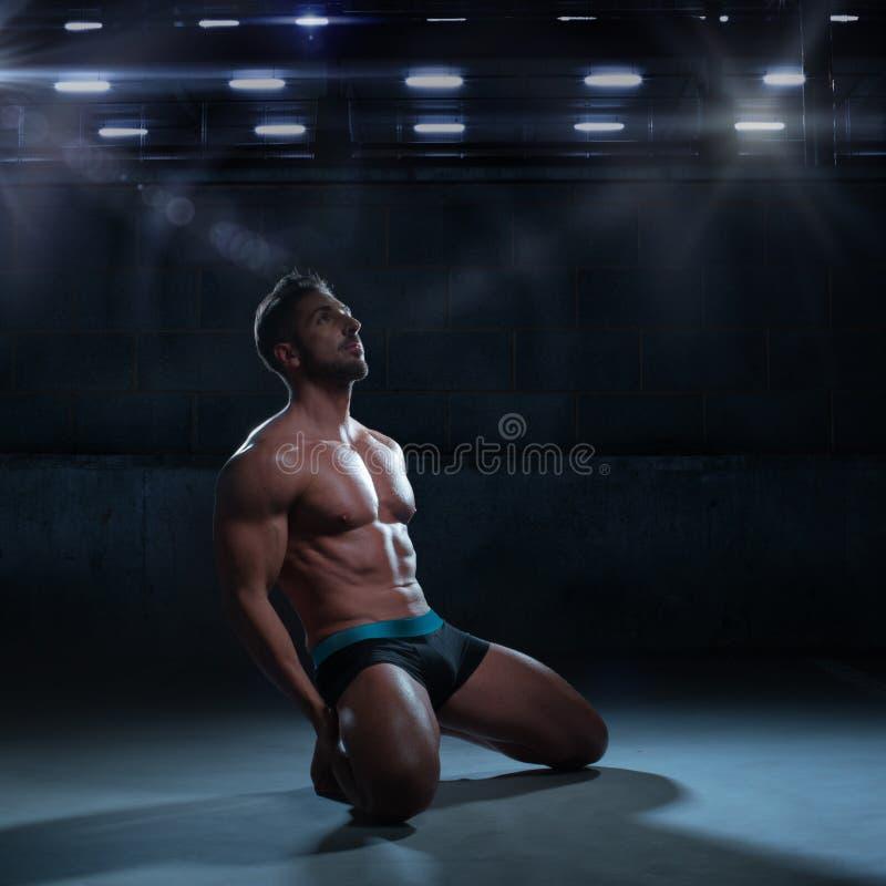 Hombre atlético pensativo atractivo que se arrodilla en el piso foto de archivo libre de regalías