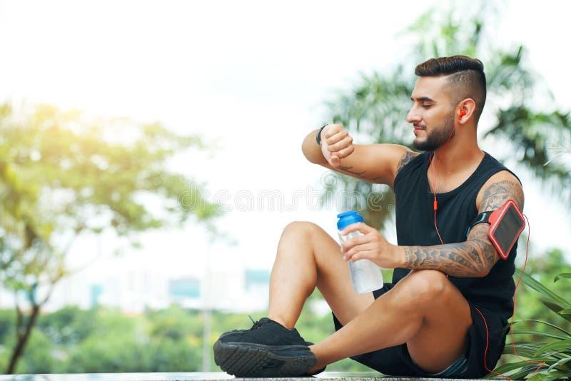 Hombre atlético que comprueba el smartwatch al aire libre foto de archivo libre de regalías