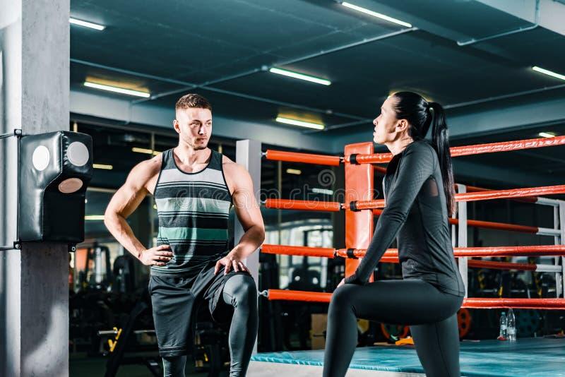 Hombre atl?tico que habla con una mujer de los deportes en el gimnasio Entrenamiento de la aptitud Comunicaci?n entre la gente fotos de archivo