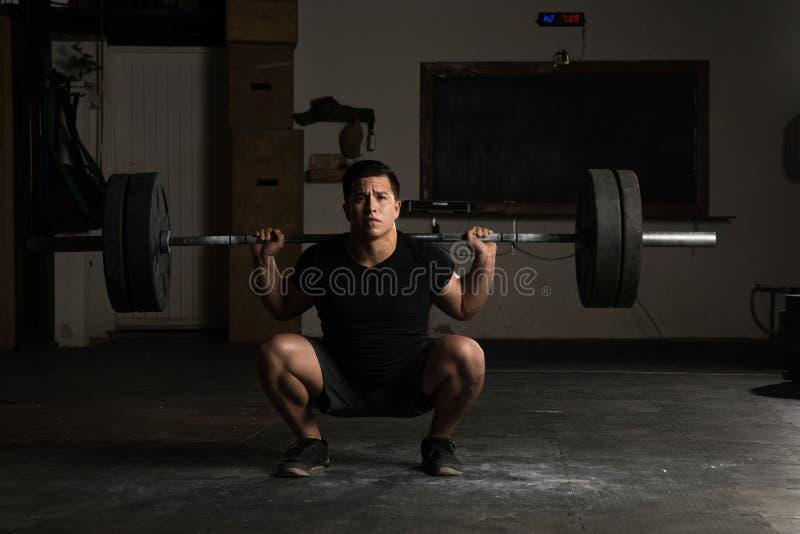 Hombre atlético que hace posiciones en cuclillas del barbell fotografía de archivo