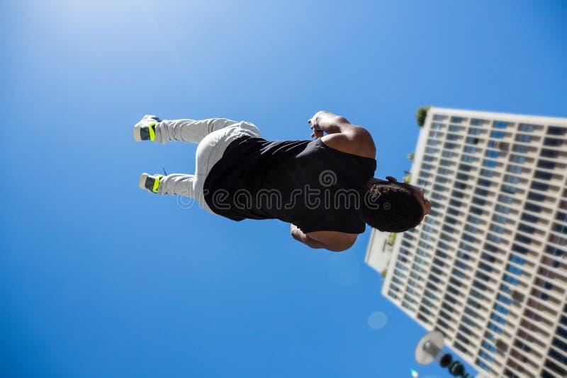 Hombre atlético que hace salto mortal hacia atrás en la ciudad fotos de archivo