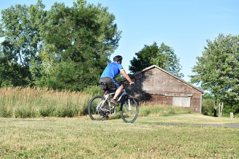 Hombre atlético que resuelve la bici que monta fotografía de archivo