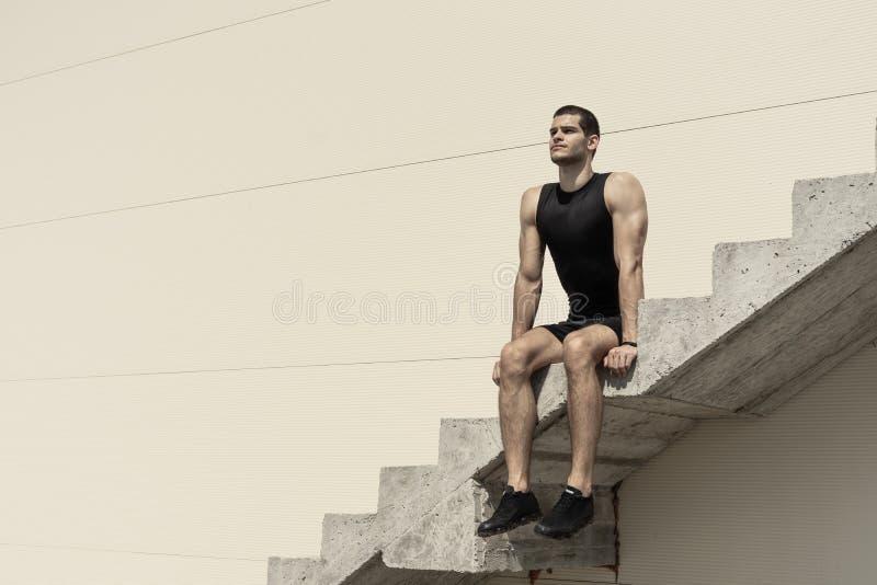 Hombre atlético que se sienta en las escaleras concretas ascendentes foto de archivo libre de regalías