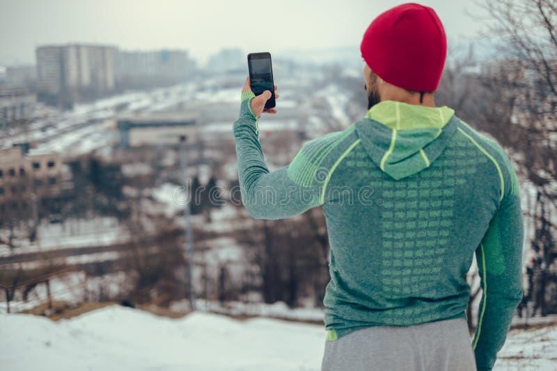 Hombre atlético que toma la foto del paisaje urbano con el teléfono en día de invierno imagen de archivo libre de regalías