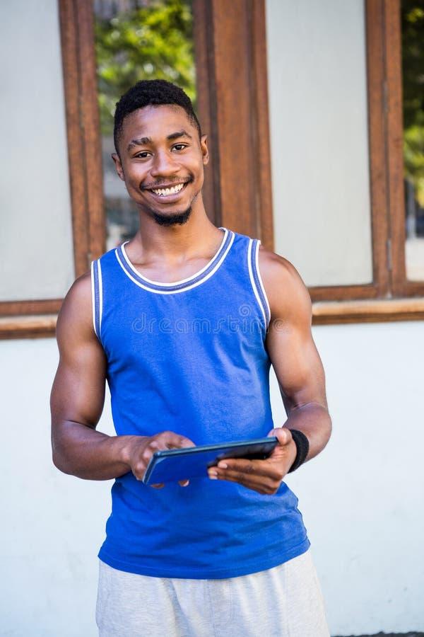 Hombre atlético sonriente que usa la tableta foto de archivo