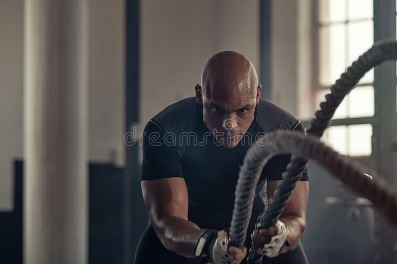 Hombre atlético usando cuerda de la batalla en el gimnasio imágenes de archivo libres de regalías