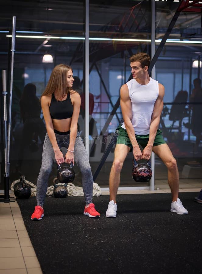 Hombre atlético y mujer que realizan un ejercicio funcional con los kettlebells en un fondo del club de fitness Concepto de los d imagen de archivo