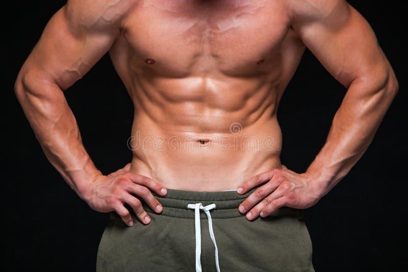 Hombre atl?tico fuerte - modelo de la aptitud que muestra su cuerpo perfecto aislado en fondo negro con el copyspace Bodybuilder foto de archivo