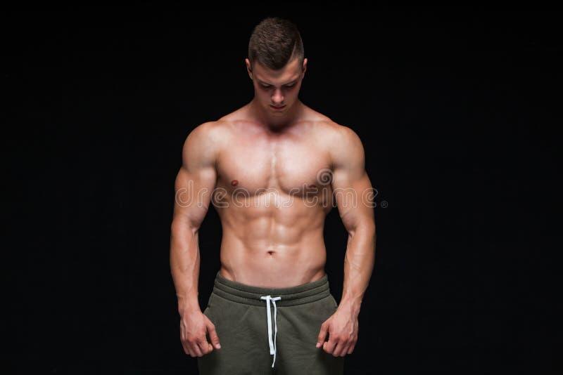 Hombre atl?tico fuerte - modelo de la aptitud que muestra su cuerpo perfecto aislado en fondo negro con el copyspace Bodybuilder imagen de archivo libre de regalías