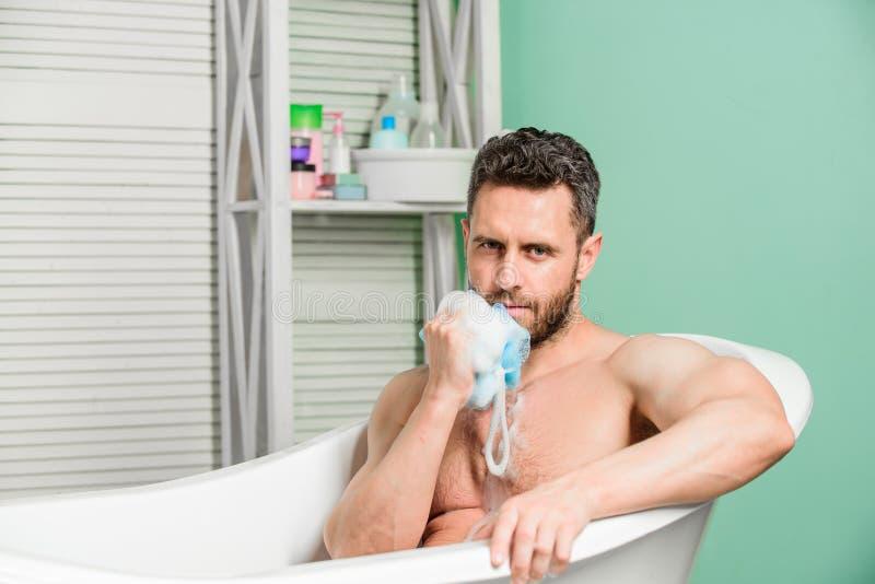 Hombre atractivo con el baño de la toma de la esponja Higiene personal Tome la higiene del cuidado La preparaci?n personal est? l imágenes de archivo libres de regalías