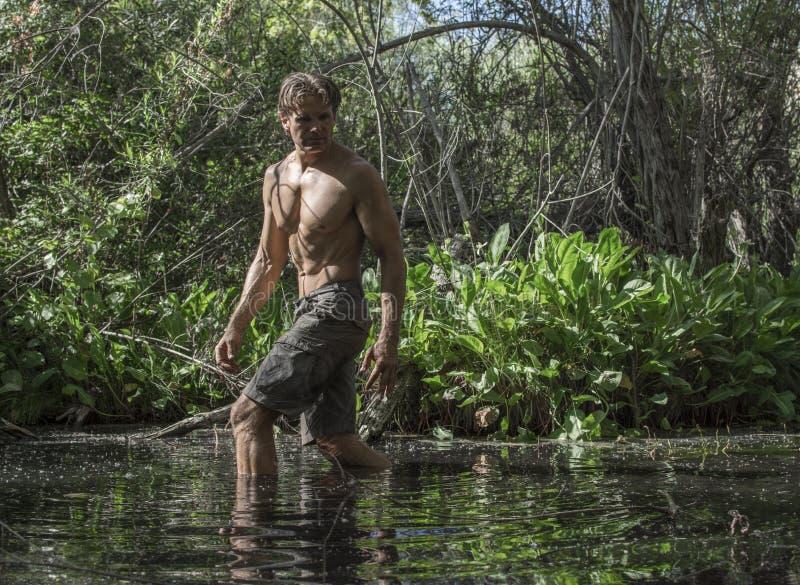 Hombre atractivo de la aventura que vadea a través de pantano fotografía de archivo
