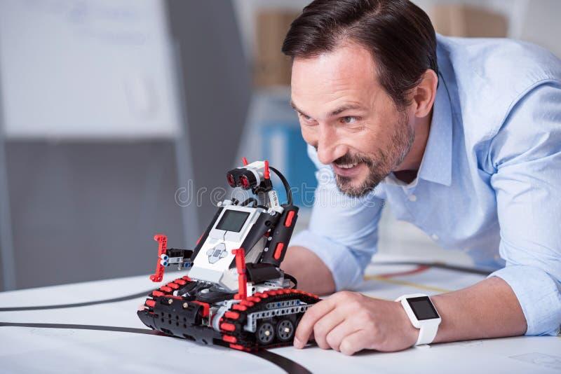 Hombre atractivo de mediana edad que lanza un robot imagen de archivo libre de regalías