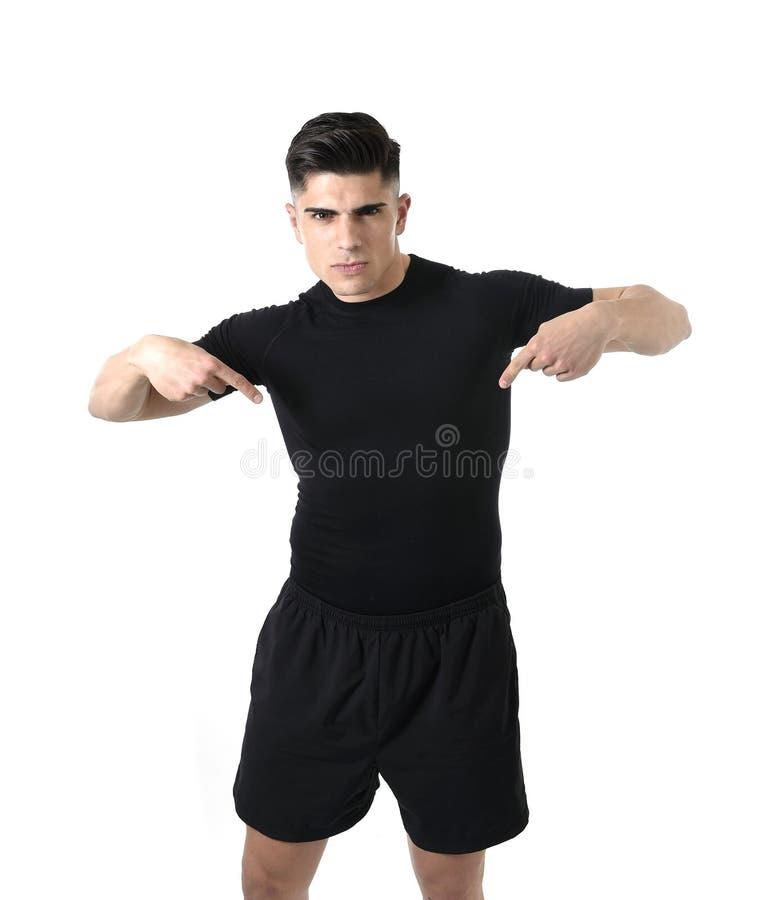 Hombre atractivo del deporte que señala en su camiseta negra con el espacio de la copia para añadir el logotipo del club de salud fotos de archivo libres de regalías