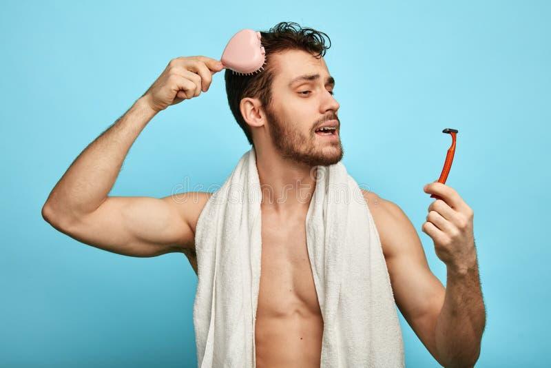 Hombre atractivo divertido que se peina el pelo por la mañana fotografía de archivo
