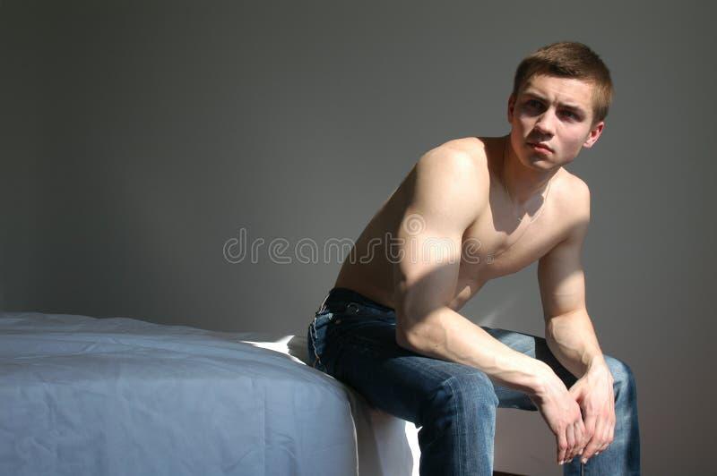 Hombre atractivo en el dormitorio fotografía de archivo