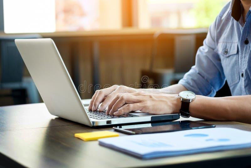 Hombre atractivo en el negocio casual que se sienta en una tabla que trabaja encendido foto de archivo