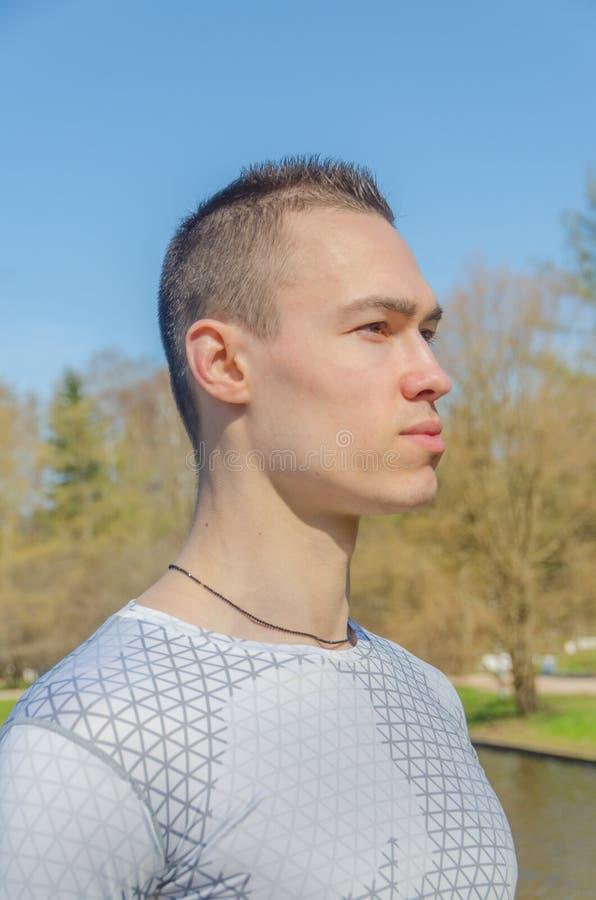 Hombre atractivo en la ropa de deportes blanca, primer imagen de archivo