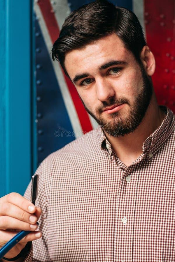 Hombre atractivo joven con la maquinilla de afeitar recta imagen de archivo