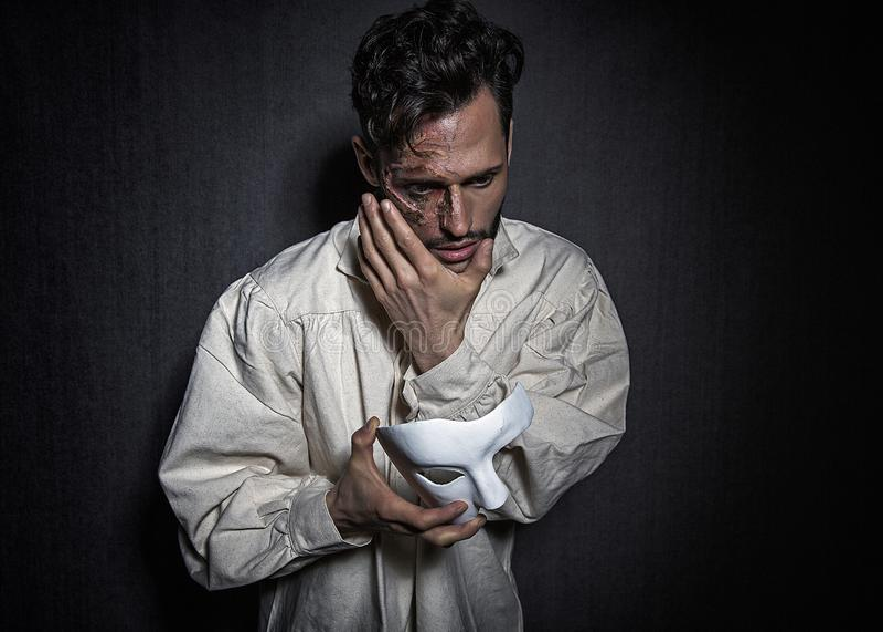 Hombre atractivo joven con las cicatrices de las quemaduras, llevando a cabo un teatro blanco como máscara imagen de archivo libre de regalías