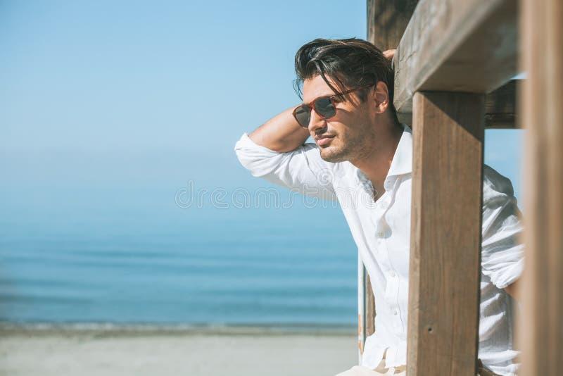 Hombre atractivo joven con las gafas de sol que miran hacia fuera sobre el mar durante el verano fotografía de archivo libre de regalías