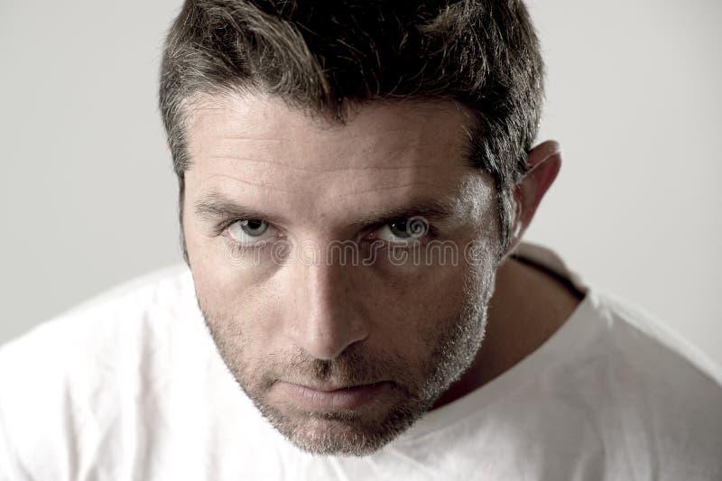 Hombre atractivo joven con los ojos azules que parecen enojados y enojados en la emoción y el trastorno de la rabia fotografía de archivo