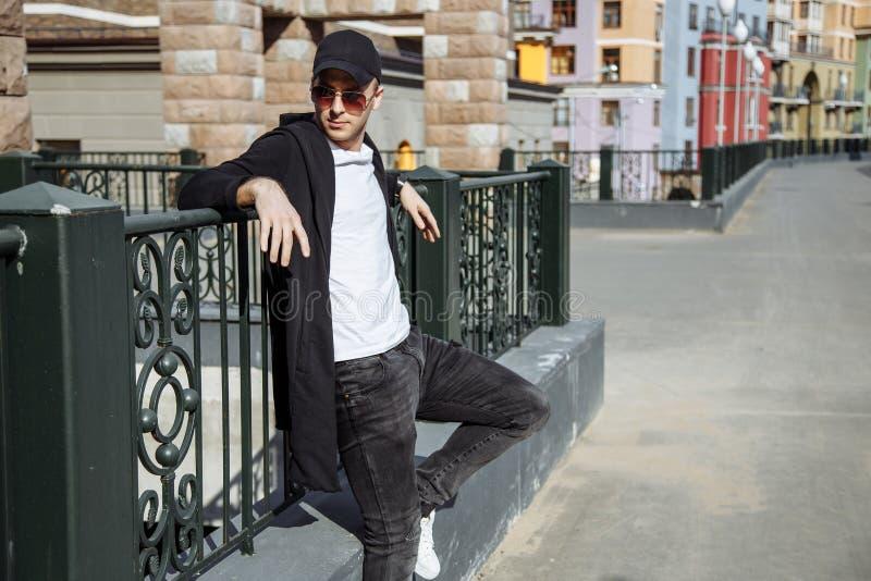 Hombre atractivo joven en gafas de sol en fondo urbano foto de archivo libre de regalías