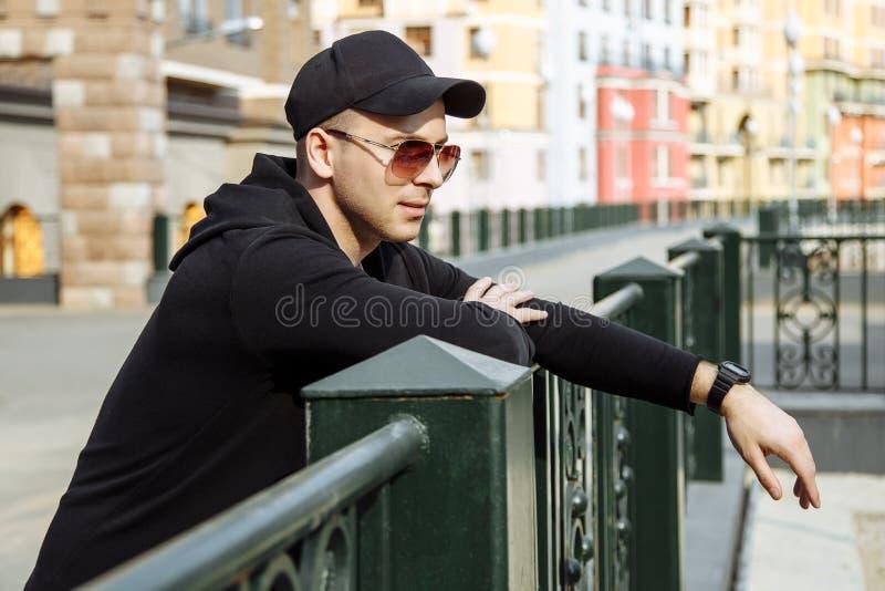 Hombre atractivo joven en gafas de sol en fondo urbano fotografía de archivo libre de regalías