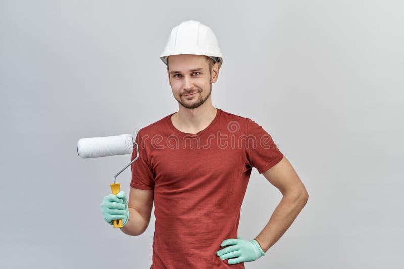 Hombre atractivo joven en la camisa roja, el casco protector blanco y los guantes sosteniendo el rodillo para pintar con la expre foto de archivo libre de regalías