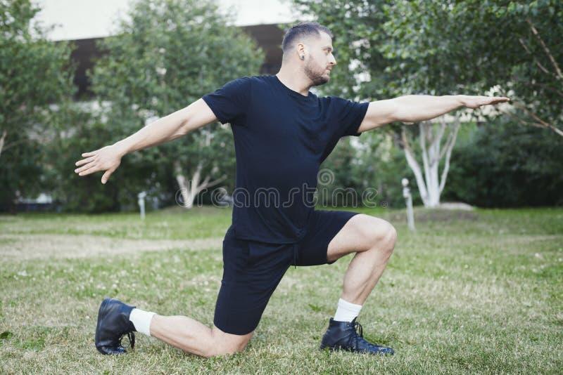 Hombre atractivo joven que hace la estocada al aire libre en el parque con las manos extendidas fotografía de archivo