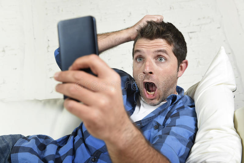 Hombre atractivo joven que miente en casa sofá usando Internet en el teléfono móvil que parece sorprendido y chocado foto de archivo