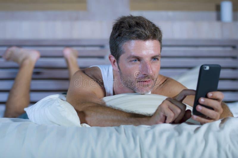 Hombre atractivo joven que miente en la cama feliz y relajada usando el teléfono móvil de Internet que envía el texto en el medio fotos de archivo libres de regalías