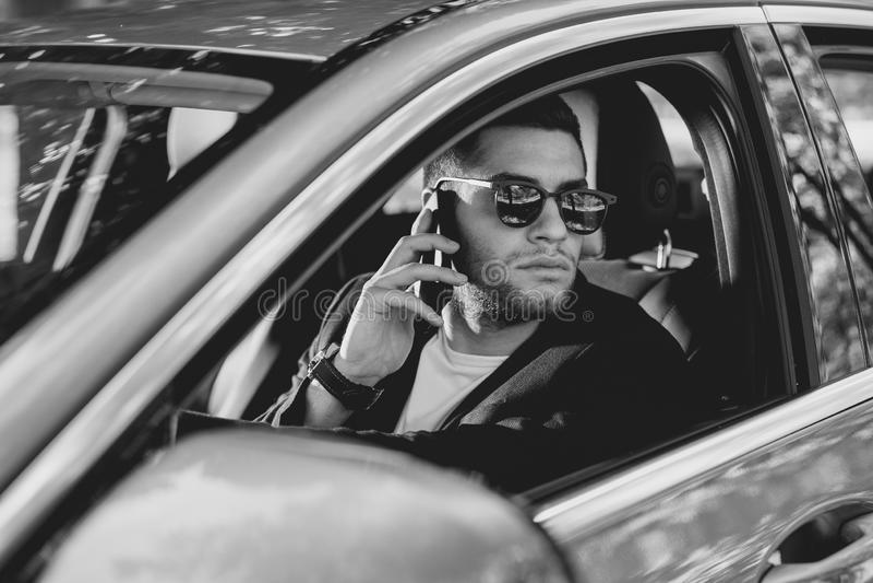 Hombre atractivo joven usando el teléfono móvil en coche imagen de archivo libre de regalías