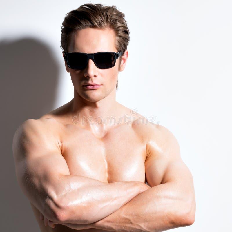 Hombre atractivo muscular en vidrios con los brazos cruzados fotografía de archivo libre de regalías