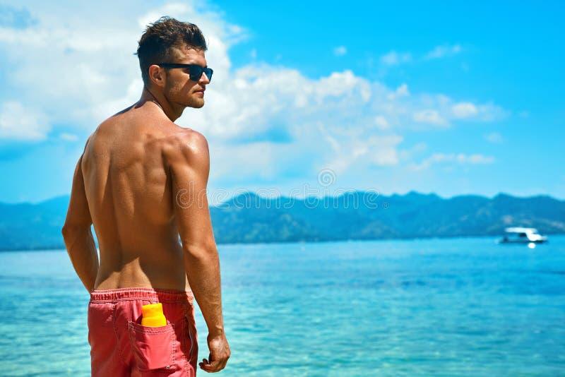 Hombre atractivo que broncea con crema de piel de Sunblock en la playa del verano imagen de archivo libre de regalías